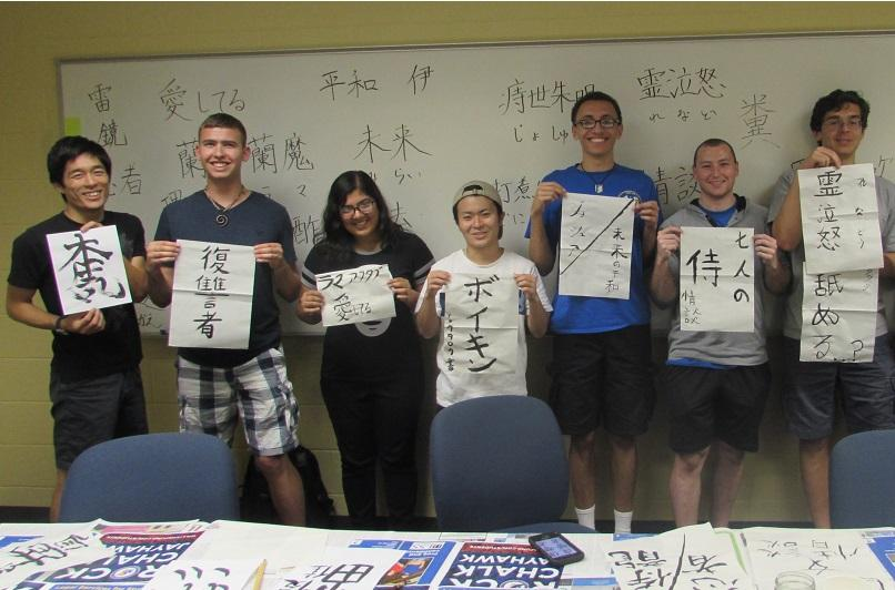 Group photo of students and instructor Masanori Shiomi holding up their Japanese calligraphy works.